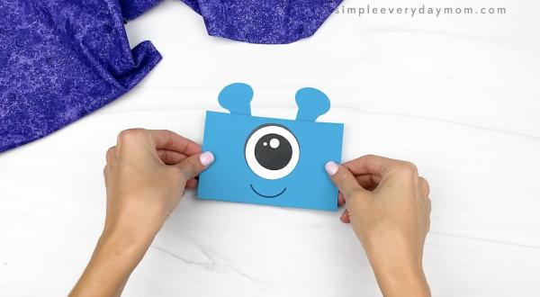 hand gluing antennae to alien paper bag puppet craft