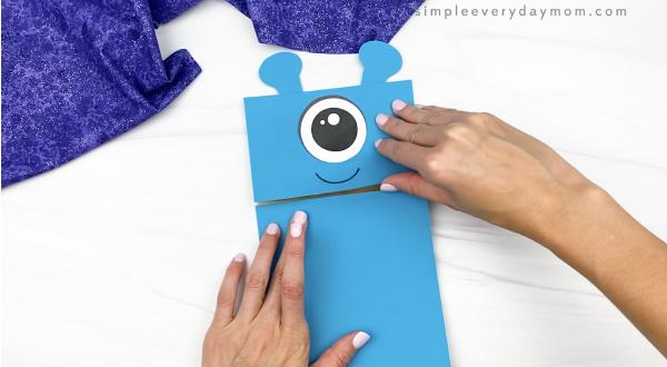 hand gluing body to alien paper bag puppet craft