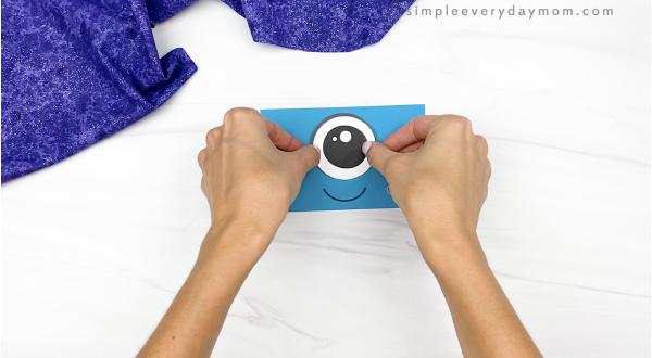 hand gluing eye to alien paper bag puppet craft