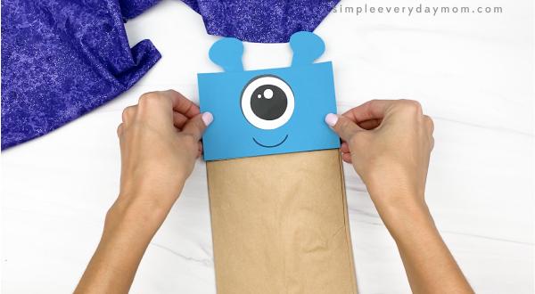 hand gluing head to alien paper bag puppet craft