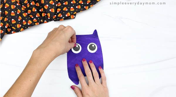 hand gluing eyes to paper plate bat craft