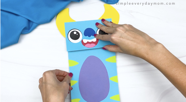 hand gluing body to monster paper bag craft