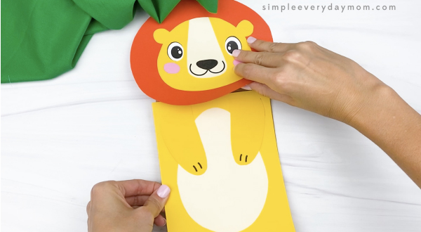 hand gluing body to paper bag lion craft