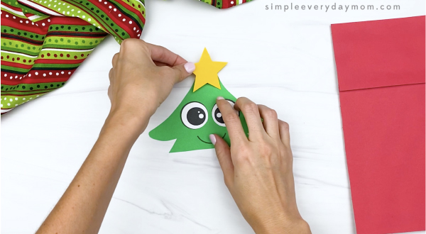 hand gluing star to paper bag Christmas tree craft
