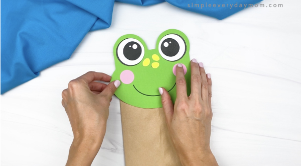 hand gluing head to paper bag frog craft