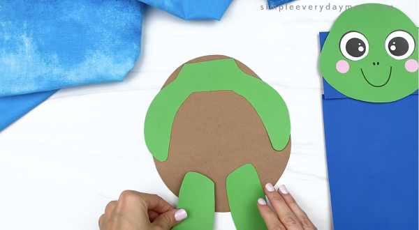 hand gluing legs to paper bag turtle craft
