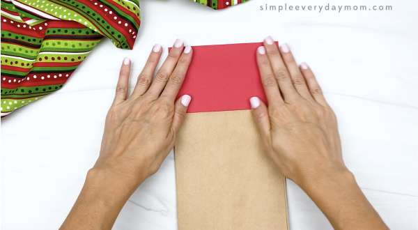 hand gluing red paper to brown paper bag