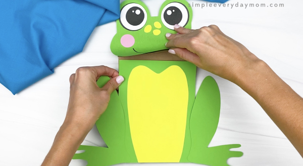 hand gluing body to paper bag frog craft