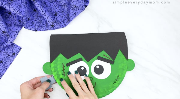 hands gluing bolts to paper plate Frankenstein face