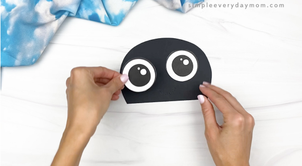 hand gluing eye to paper bag ladybug head