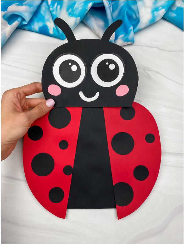 hand holding paper bag ladybug craft