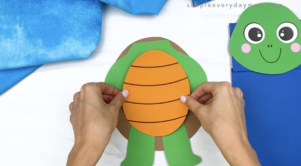 hand gluing belly to paper bag turtle craft