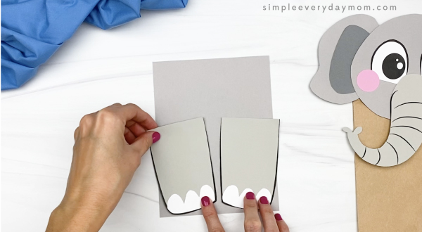 hand gluing legs to paper bag elephant craft