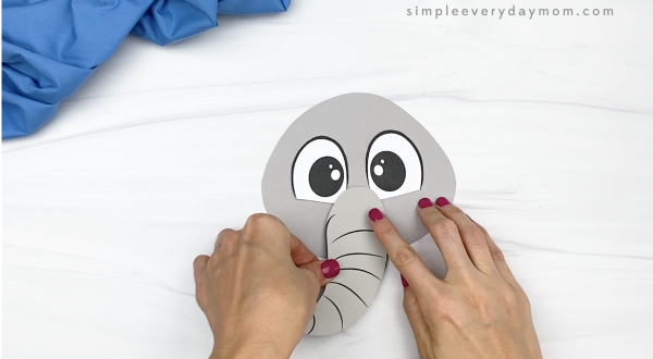 hand gluing trunk to paper bag elephant craft