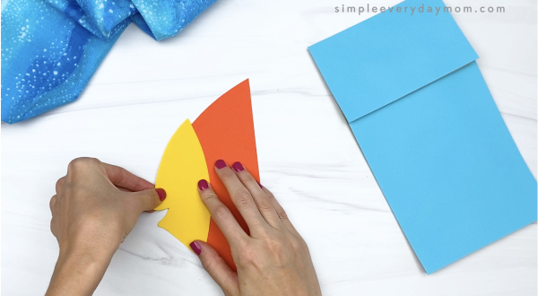 hand gluing face to paper bag fish craft
