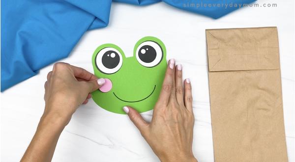 hand gluing cheek to paper bag frog head