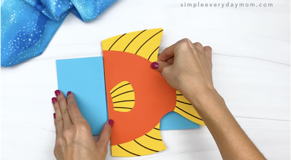 hand gluing body to paper bag fish craft