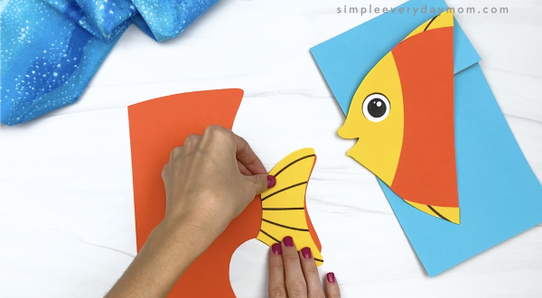 hand gluing tail fin to paper bag fish craft