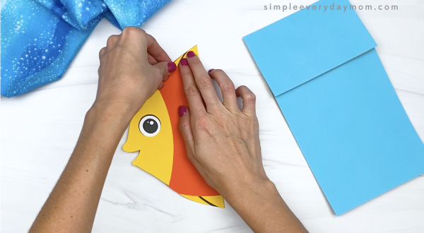 hand gluing dorsal fin to paper bag fish craft