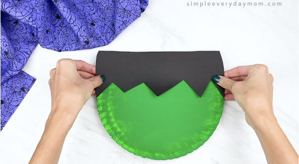 hands gluing Frankenstein hair to paper plate
