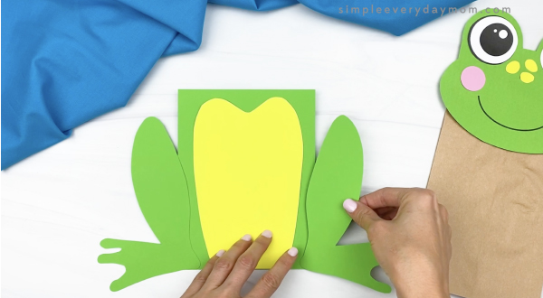 hand gluing leg to paper bag frog craft