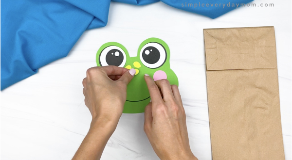 hand gluing spot to paper bag frog head