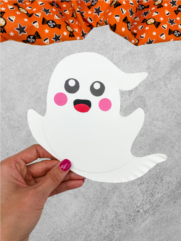 hand holding paper plate ghost