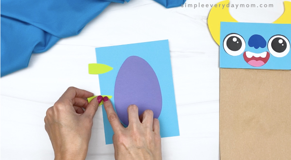 hand gluing stripes to monster paper bag craft
