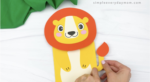 hand gluing tail to paper bag lion craft