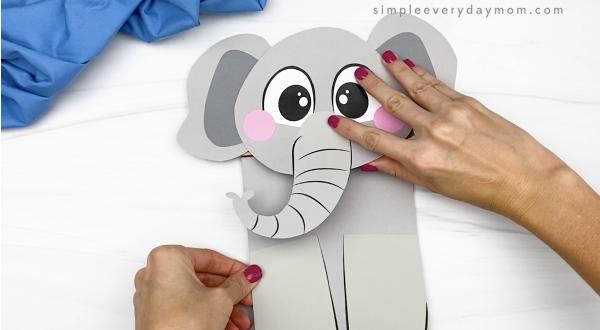 hand gluing body to paper bag elephant craft