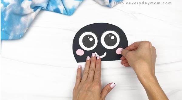 hand gluing cheek to paper bag ladybug head