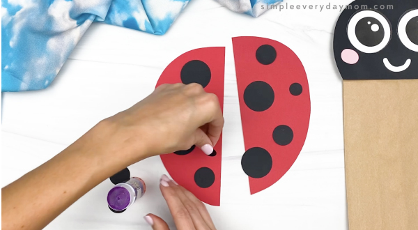 hand gluing spots to paper bag ladybug wings