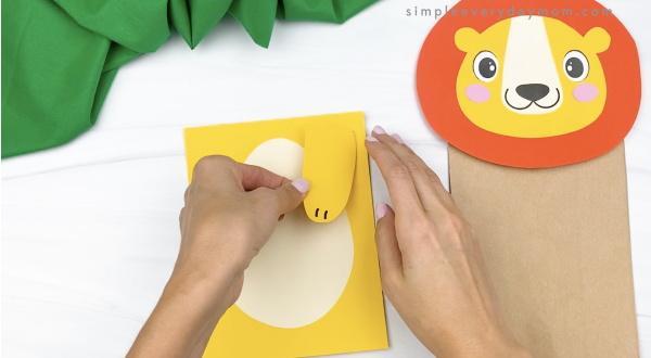 hand gluing arm to paper bag lion craft