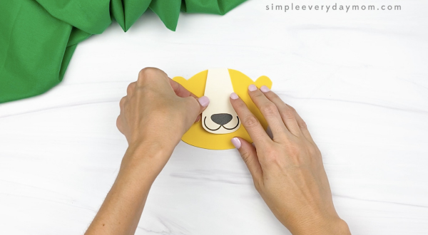 hand gluing nose and mouth to paper bag lion craft