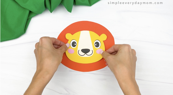 hand gluing head to mane of paper bag lion craft