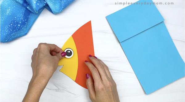 hand gluing eye to paper bag fish craft