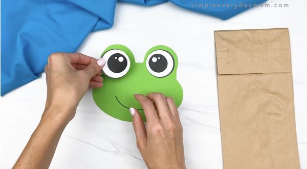 hand gluing eye to paper bag frog head