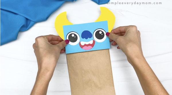 hand gluing monster head to paper bag