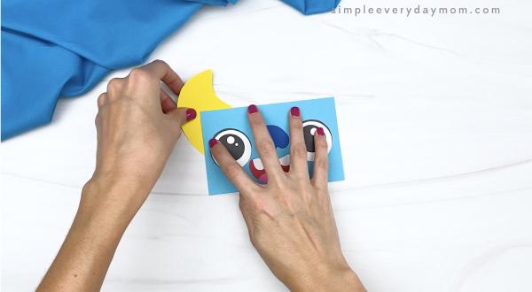 hand gluing horns to paper bag monster head