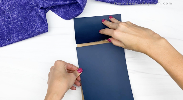 hand gluing dark blue paper to brown paper bag