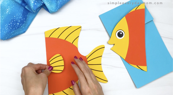 hand gluing fin to paper bag fish craft