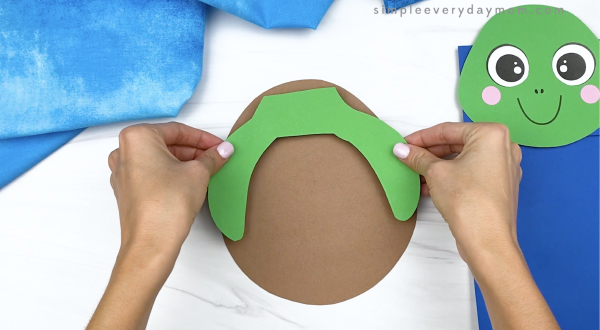 hand gluing arms to paper bag turtle craft