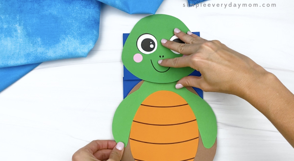 hand gluing body to paper bag turtle craft