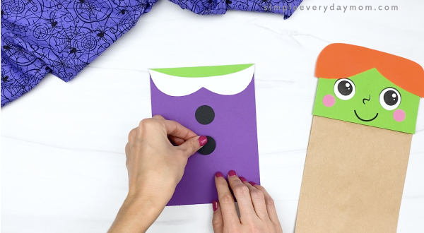 hand gluing buttons onto dress of paper bag witch craft