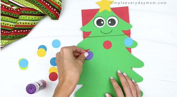 hand gluing ornaments to paper bag Christmas tree craft