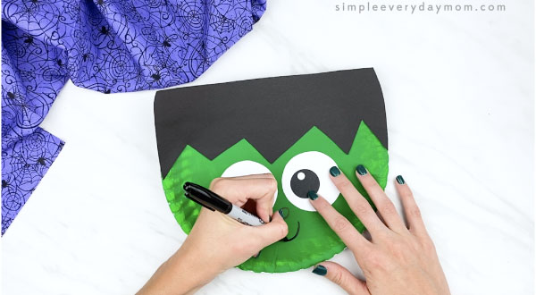 hands drawing mouth on paper plate Frankenstein face with black marker