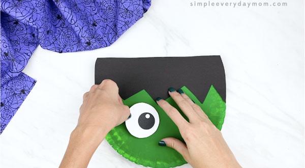 hands gluing eyes to paper plate frankenstein