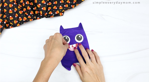 hand gluing mouth to paper plate bat craft
