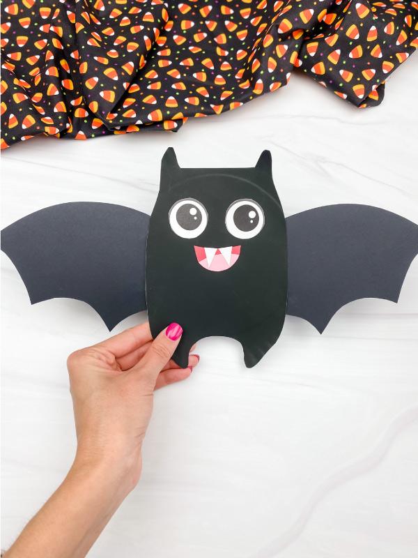 hand holding paper plate bat craft