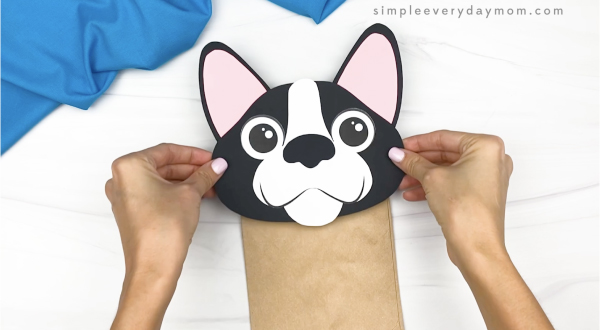 hand gluing head to paper bag dog craft